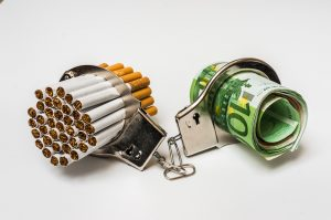 cigarettes-and-money-trapped-in-handcuffs-to-show-the-cost-of-smoking