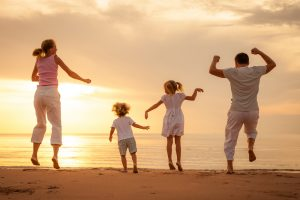 happy-family-jumping-with-joy-on-the-beach-at-sunrise