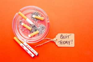 health-money-and-quit-smoking-today-tag-on-cigarettes-in-ashtray-on-red-background