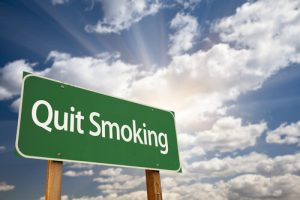 quit-smoking-road-sign-with-sun-rays-behind-white-clouds-and-blue-sky