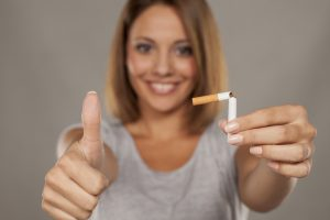 young-smiling-woman-holding-a-broken-cigarette-and-giving-thumbs-up